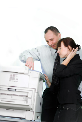Engineer shows a client how to use a photocopier feature