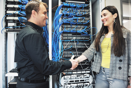 IT Guy shakes hands with a client in front of a comms cabinet